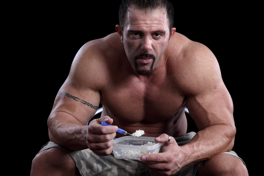 Bodybuilder eating rice against black background