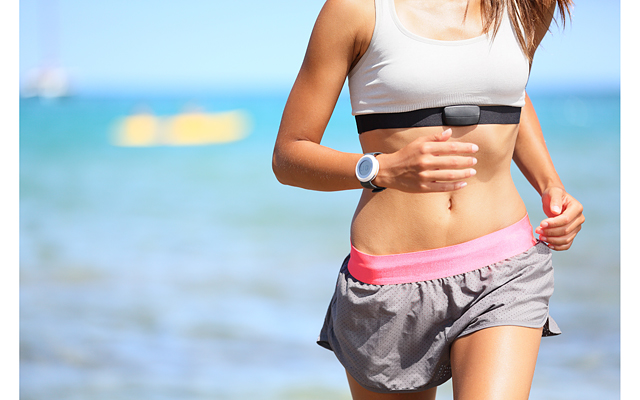 Runner woman with heart rate monitor running